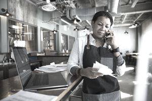 Female business owner paying bills in brewhouse