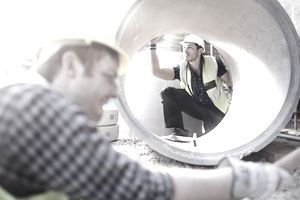 Two male construction workers in yellow vests and hard hats, one worker looking inside a large concrete pipe