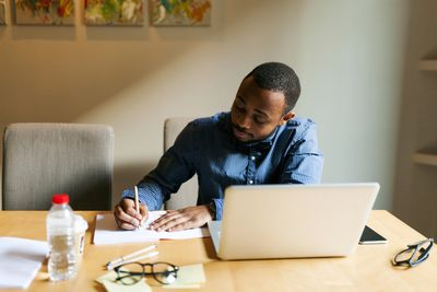 Young man at table with laptop writing in notebook
