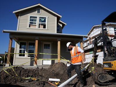 Home being dug around by construction worker