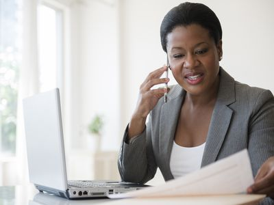 Businesswoman on a cell phone while reading paperwork, sitting at a laptop computer