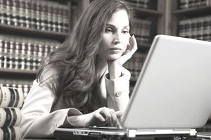Hispanic woman looking at laptop