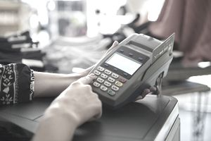 Woman using credit card terminal
