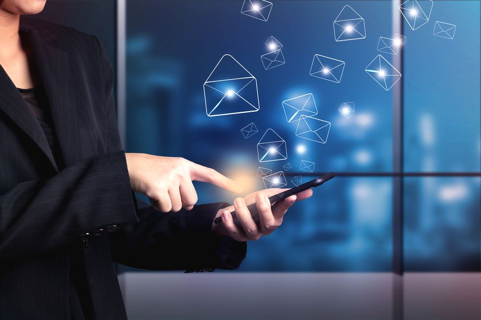 photo illustration of a woman sending email messages on a smart phone