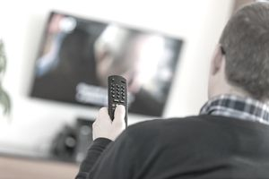 Man holding remote watching TV mounted on wall