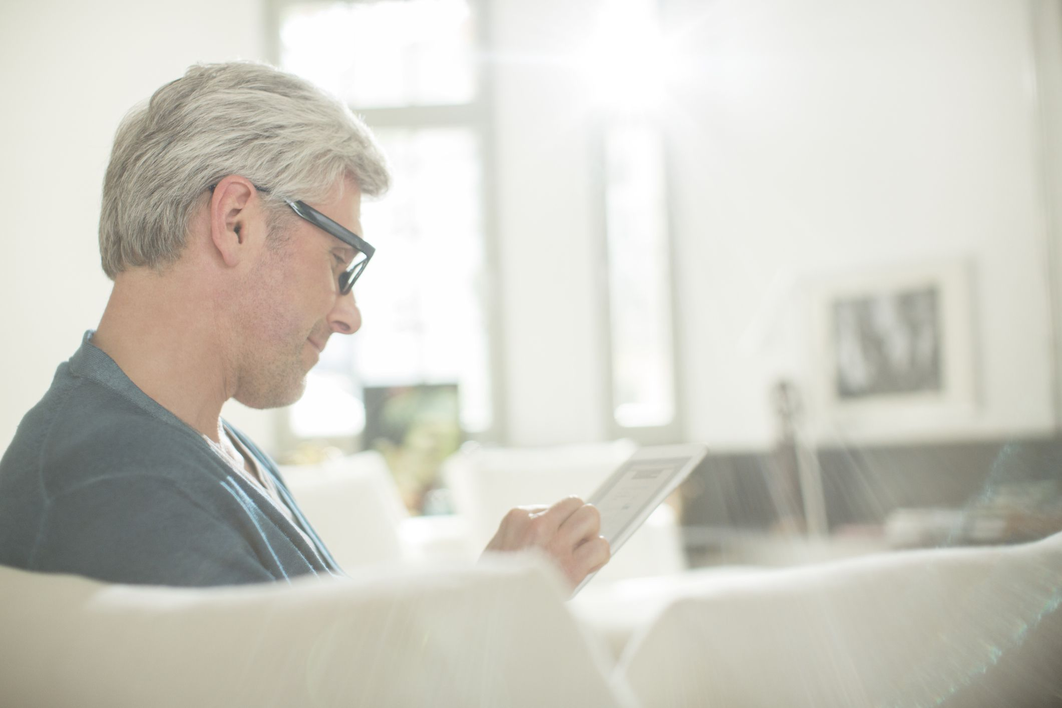 Man reading on tablet in living room