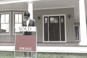 "Real estate agent putting ""SOLD"" sign on lawn"