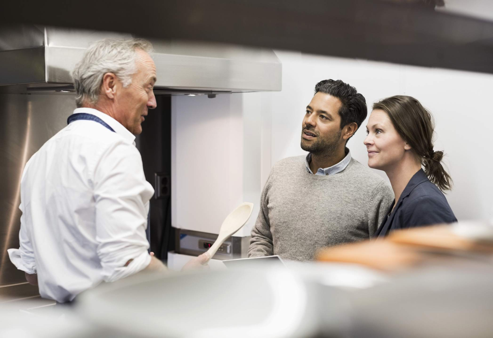 Chef talking to business people in commercial kitchen