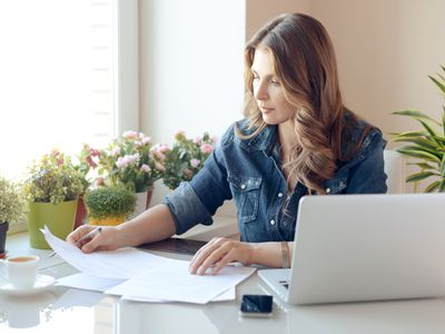 Young woman working at a desk at home with laptop and paperwork