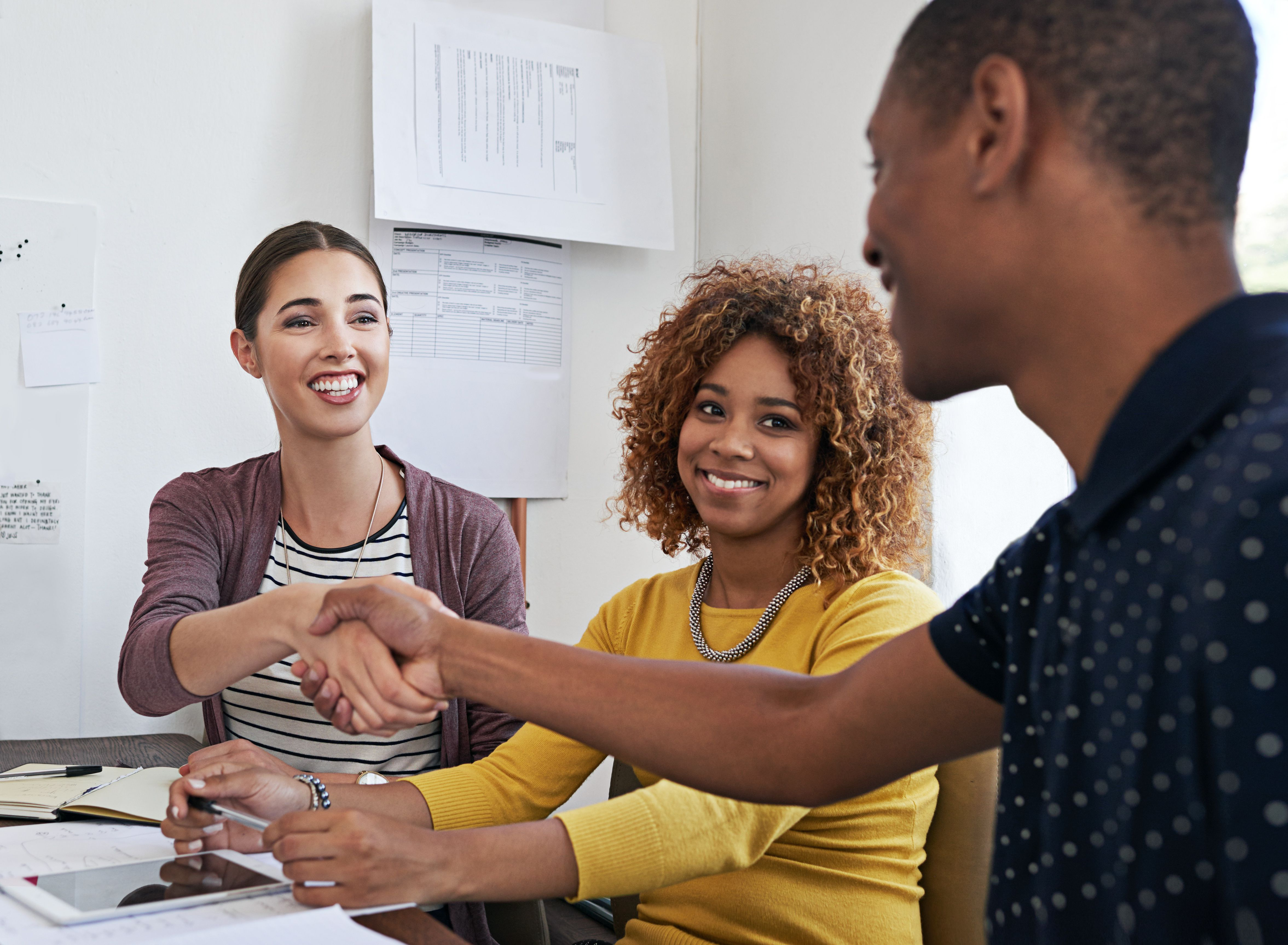 Man shaking hands with two happy female clients