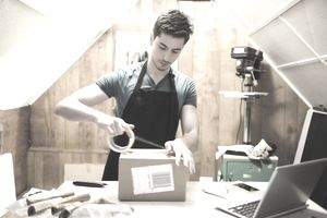 Young man using tape to prepare package for delivery