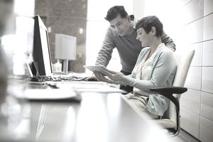 Business people working on a tablet and monitor in an office.
