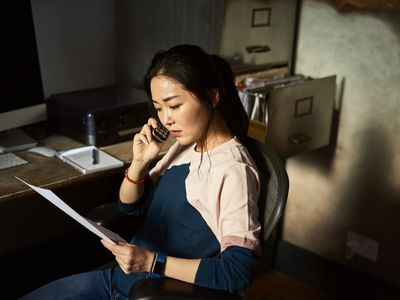 Woman on the phone with a client asking them for feedback.