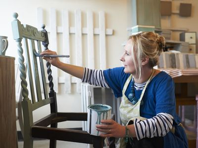 A woman refinishing a chair in her home workshop as a small business.