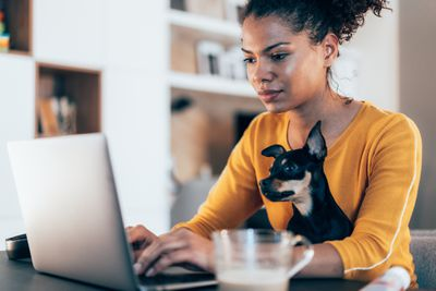 Young afro-american woman sitting with her pet dog and using laptop at home