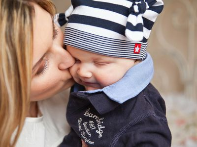 a mom kissing her baby on the cheek