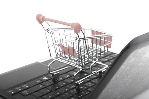 Small shopping cart sitting on a laptop keyboard
