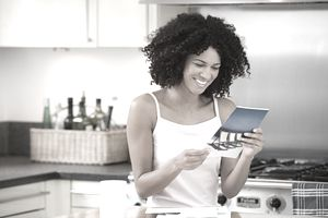 smiling woman standing in kitchen reading a promotional brochure