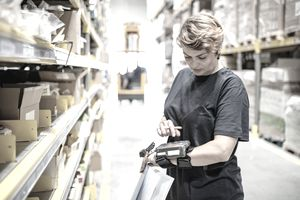 A woman conducting an inventory count in a warehouse
