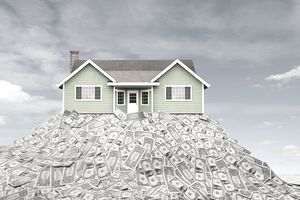 A house sitting on pile of dollar bills