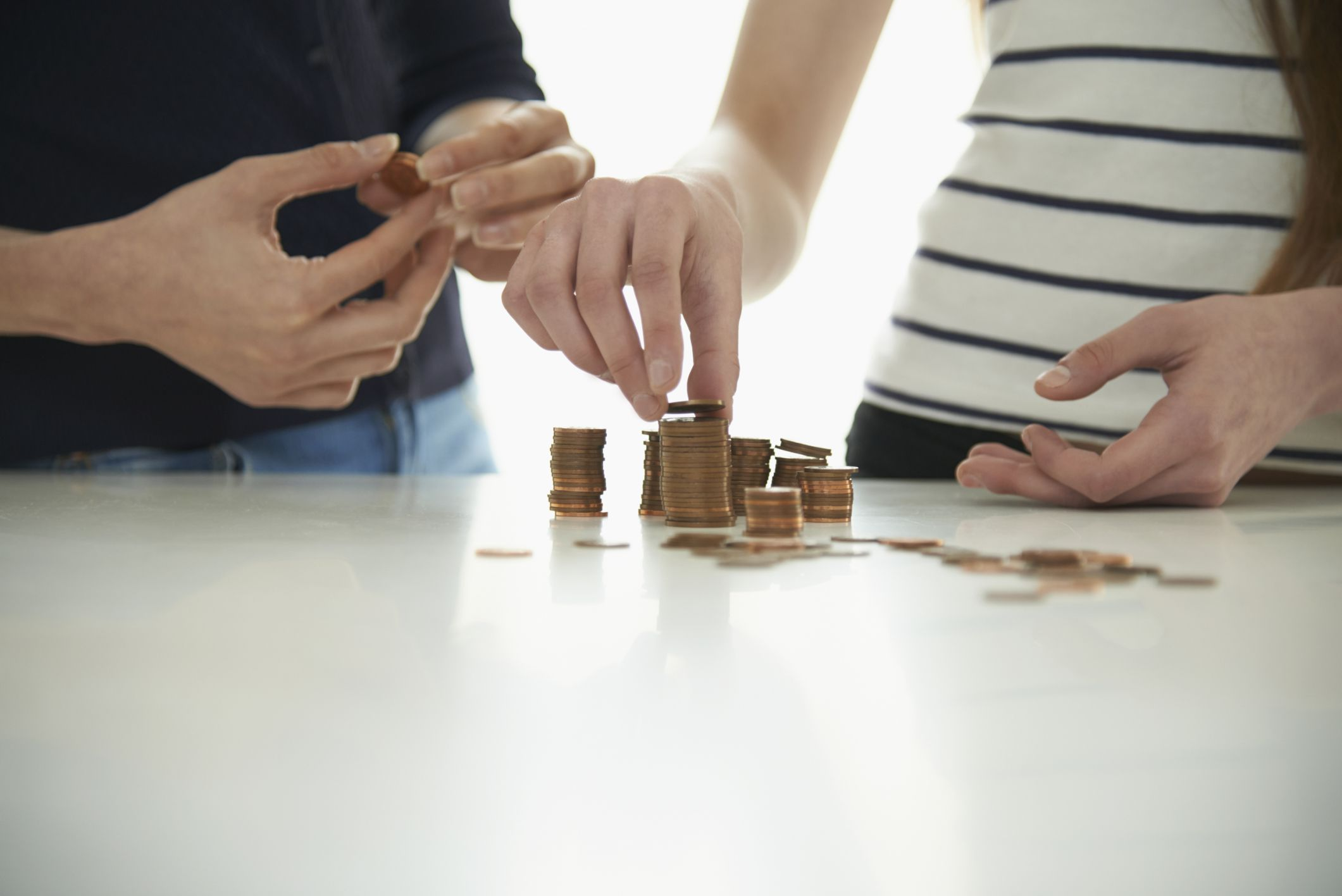 Couple budgeting funds down to the penny and stacking coins on a table top.