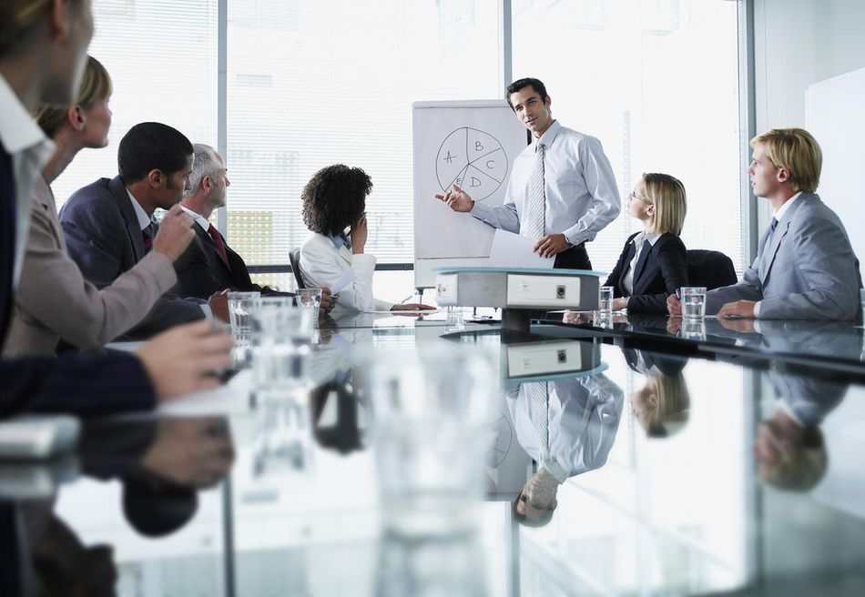 A group of office workers in a boardroom presentation