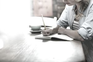 Woman writing in coffee shop