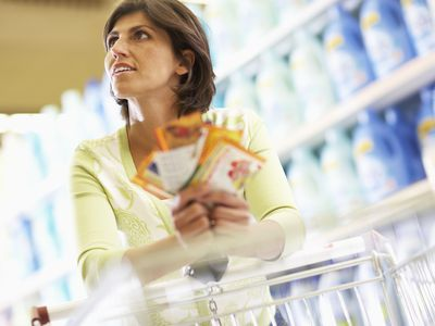 Woman Grocery Shopping Using Coupons