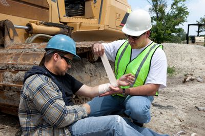 Coworker wrapping up a worker's injury on a job site which will probably lead to a workers comp claim.