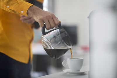 Man in orange button up pouring coffee into a cup from a pot