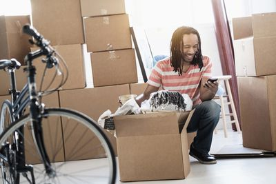 Man unpacking boxes in new home near bicycle while smiling and looking at smartphone.