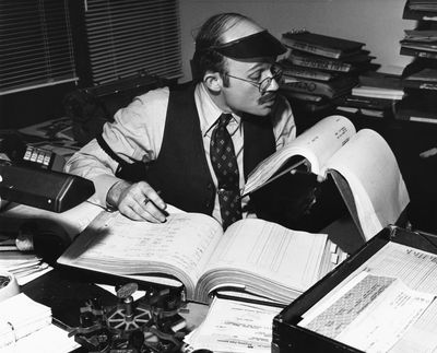 Black and white image of an accountant at a desk performing a worker's compensation audit.