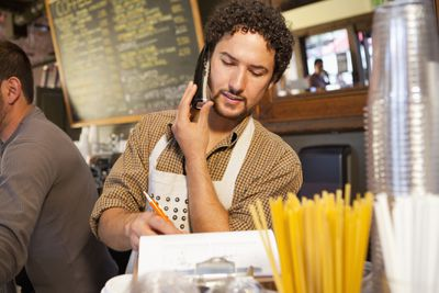 Business owner talking to accountant on the phone about his business taxes.