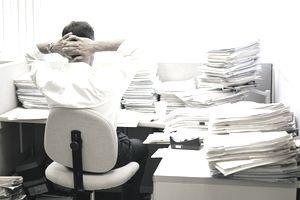 Businessman with stacks of papers at desk