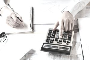 Accountant working on desk to using calculator with pen on book.
