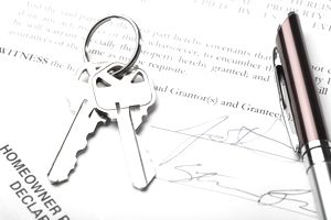 Keys and pen on a real estate contract.