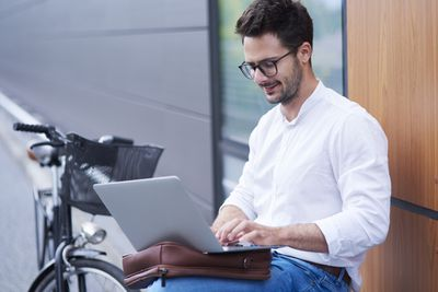 Man with glasses working on laptop next to his bike