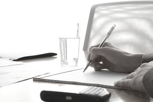 Businesswoman's hands writing on notepad in boardroom