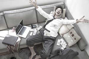 Smiling man on his couch with a laptop and lots of cash representing making money online.
