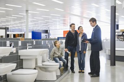 Salesman talking to family in bathroom supply store
