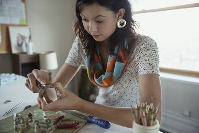 Woman sitting at her desk making jewelry