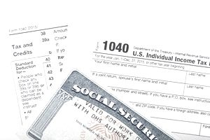 Close up of a Social Security card on top of tax forms, representing social security taxes.