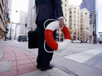 businessman in city holding life ring