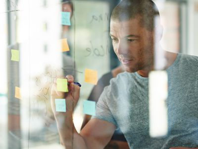 T-shirted man writing on Post-it notes stuck on glass