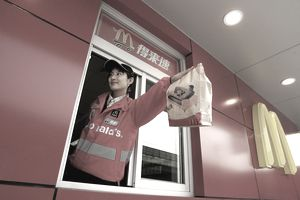 Woman serving food at a McDonald's drive-thru in Beijing