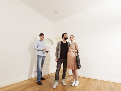 Landlord going over checklist with new tenants in an apartment