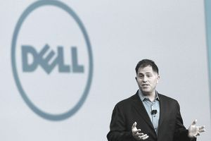 Dell executive speaking at a gathering in front of a large Dell logo.
