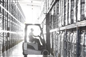 Worker operating forklift in warehouse