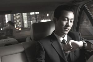 Businessman looking at watch in car