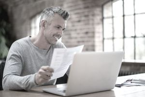 Smiling man at laptop looking at documents, interior brick walls